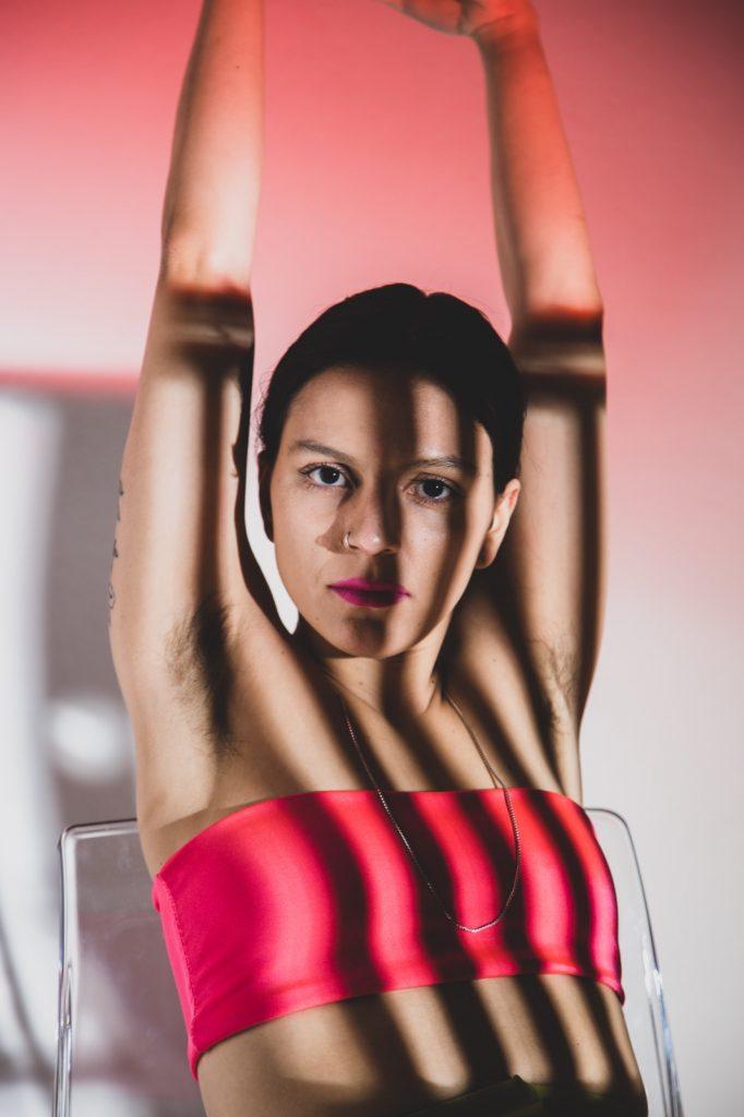 eine jungen Frau, die in gestreiften Schatten die Arme nach oben reckt