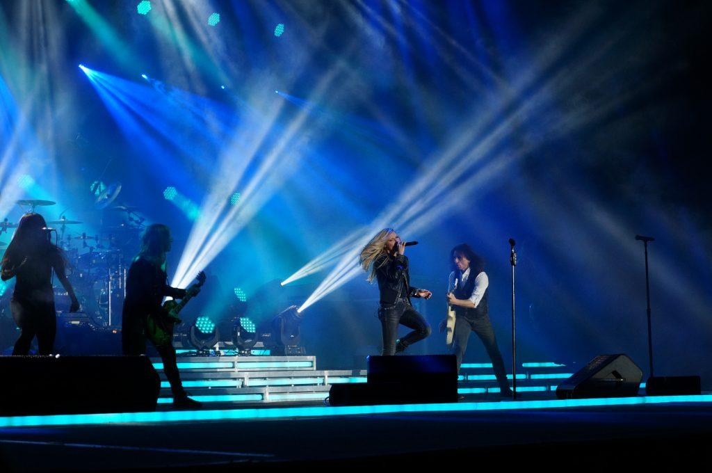 eine Metalband während eines Konzerts, der Sänger sprintet singend auf der Bühne nach vorn.
