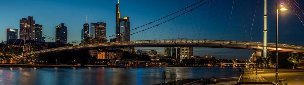 die Skyline von Frankfurt am Main am Abend in sehr expressiven Farben mit Schatten von Personen im Vordergrund
