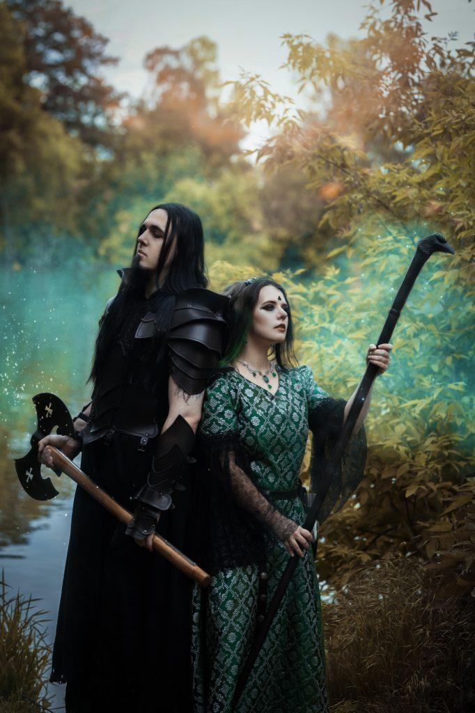 ein Mann und eine Frau in Fantasykleidung vor einem Waldhintergrund