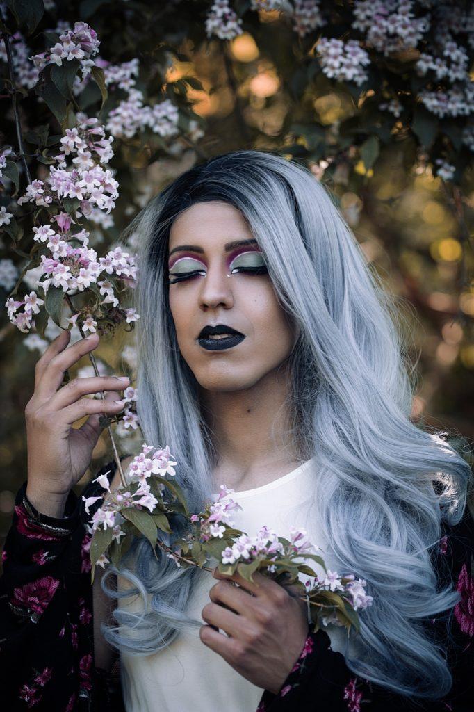 eine Person mit langen Haaren und expressivem Make-Up, die sich an Kirschblüten schmiegt